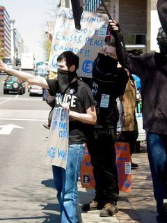 """At the corner of 14th Street and Pennsylvania Avenue, just outside the JW Marriott Hotel, a black bloc has assembled. Here, two of these masked protesters, which you may recall are the ones we encountered earlier, are holding up their signs in front of 14th Street traffic. One of the most memorable things to happen while covering the black bloc was when a man riding in a passing car yelled out the window, """"Why don't you love America?"""""""