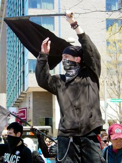 Quite a few black bloc protesters waved black and red flags, though black flags tended to predominate. This protester is waving his flag in front of cars on 14th Street.