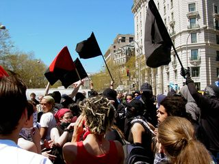 """In the street, some protesters waved their black flags high as a chant of """"Ain't no power like the power of the people, cause the power of the people don't stop!"""" rang out."""