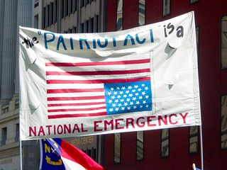 Flying the flag upside down is considered a distress signal, and according to the makers of this sign, the Patriot Act being in place is indeed an emergency.