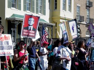 Protesters continued along in a constant stream down the street, carrying all manner of signage...