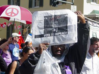 """This man holds up a sign saying """"Vote To Impeach"""", with Bush decorated up not as Hitler, but rather as the spawn of Satan."""
