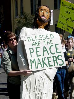 """Another protester holds up a large sculpture of Jesus, holding a sign saying """"Blessed are the peacemakers""""."""