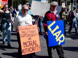 """After the Clinton-era sex scandals, the notion came up of the president's need to be a moral leader as well as a political leader. This protester simply reminds us of Rome, and how military superiority does not make moral authority, while her companion simply carries a sign stating """"LIAR""""."""