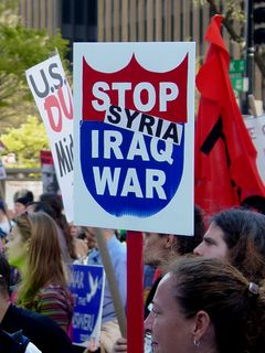"""A protester with one of the aforementioned """"Stop Iraq War"""" signs has this time added the word """"Syria"""" to the sign, wondering whether this was the next stop in the war on terror."""