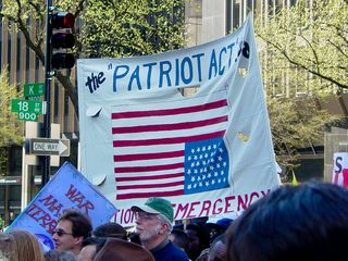 Other familiar scenes make their appearance, as the Patriot Act banner and corporate logo flag finish the protest route.