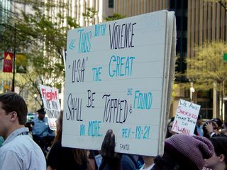 This protester's sign shows the text of Revelation 18:21 from the New Testament.