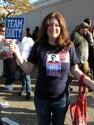 """A woman wears a """"Keep Fear Alive"""" shirt while holding a """"TEAM SANITY"""" sign."""