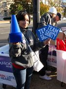 """A woman hands out blue """"TEAM SANITY"""" signs and bullhorns."""