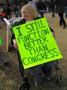 """A woman in a wheelchair holds a sign reading, """"I still function better than Congress""""."""