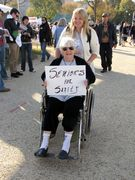 """A woman in a wheelchair holds a sign reading, """"Seniors for Sanity""""."""