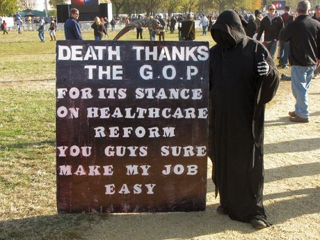 """A person dressed as the Grim Reaper holds a sign reading, """"Death thanks the GOP for its stance on healthcare reform. You guys sure make my job easy."""""""