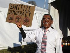 """A person wearing an Obama mask holds a sign encouraging people to """"Sanitize Democracy""""."""