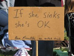 """Sign about witch trials, stating, """"If she sinks, she's OK""""."""