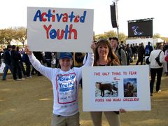"""A mother and son hold up their signs. The son's message is about being an """"activated youth"""", while the mother's message is that the only thing to fear is """"foxes and mama grizzlies""""."""