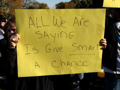 """A woman holds a sign reading, """"All we are saying is give smart a chance."""""""