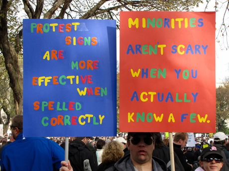 A man holds two signs - one reminding everyone why it's important to spell the messages on your protest signs correctly, and the other about minorities.