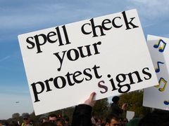 Another sign reminds people to always make sure that their protest sign messages are spelled correctly.
