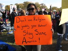 A woman holds a protest sign encouraging sanity by not using religion to justify hatred.