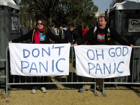 """A couple holds opposing banners. One person holds a banner stating """"DON'T PANIC"""", while the other holds a banner stating, """"OH GOD PANIC""""."""