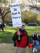 A man holds a sign challenging right-wingers' interpretation of evolution.