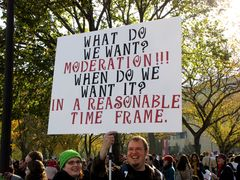 """In a spoof of the typical chant of """"What do we want? [Whatever]! When do we want it? NOW!"""" a man holds a sign saying, """"What do we want? Moderation! When do we want it? In a reasonable time frame."""""""