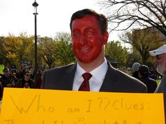 A man spoofs then-House Minority Leader John Boehner with an orange-painted face, and a sign encouraging viewers to guess who he is supposed to be.