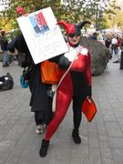 A woman wears a jester outfit while holding up a sign advocating for Harvey Dent, aka Two-Face from the DC Comics universe.