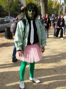 A man dresses in green tights, white shoes, a pink tutu, a green jacket, black shirt, and white tie, and has his face painted green. I don't know what else to say about this outfit.
