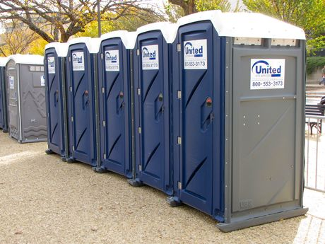 A row of portable toilets - one of many provided all around the event for attendees.