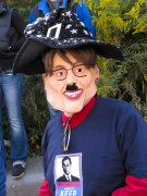 A woman wears a Sarah Palin mask with an added Hitler mustache.