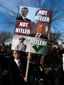 A man in a business suit holds a sign indicating that Barack Obama and Glenn Beck both are not Adolf Hitler.