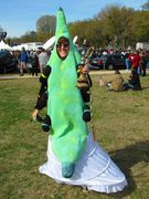 A woman wears a green banana costume while also holding a hookah in one hand.
