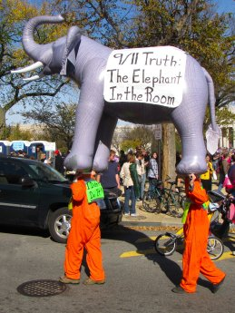 Two people in orange jumpsuits carry a large inflatable elephant with banners discussing the 9/11 Truth movement.