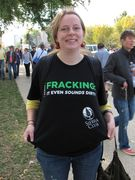 """A woman wears a shirt stating opposition to hydraulic fracturing, better known as """"fracking""""."""