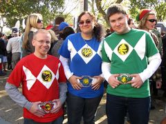 A group poses while wearing shirts designed to resemble the Mighty Morphin Power Rangers uniforms. This shirt design is based on the suits seen in the movie, as the television show's uniforms never had chest emblems.