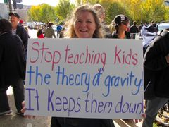 A woman holds a sign playing on gravity and education.