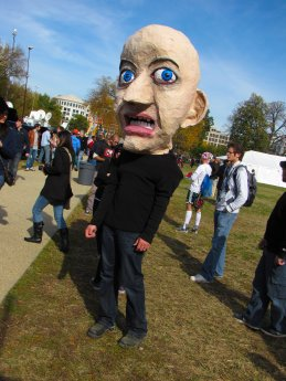 A man wears a giant papier-mâché head, designed to look frightened.