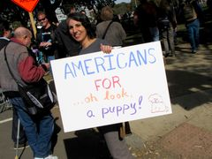 A woman holds up an easily-distracted sign.