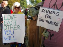 """One woman holds up a sign saying, """"Love Each Other You Will"""", while another, dressed as a character from Gremlins, holds up a sign reading, """"Seniors For Truthiness""""."""