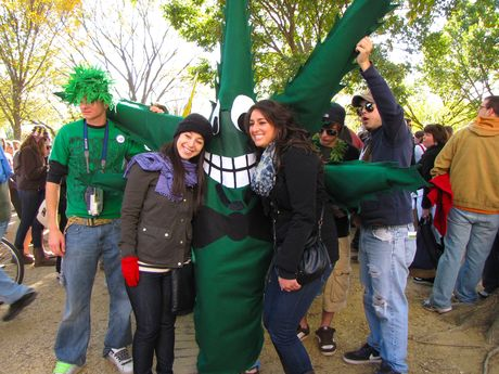 Two women pose with a person dressed as a giant marijuana leaf.