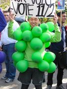 Two men dress as grapes, with plays on jams and raisins on their signs.