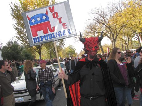 """A man dresses in a way to resembling a devil, while carrying a sign reading, """"VOTE REPUBLICAN""""."""