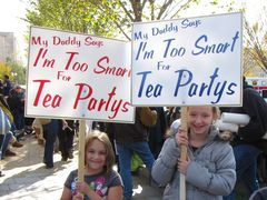 """Two children carry signs that say, """"My Daddy Says I'm Too Smart For Tea Partys"""". Unfortunately, this sign is grammatically incorrect, as the final word should be written as """"Parties""""."""