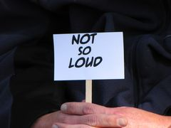 """A person holds a small sign stating, """"Not So Loud""""."""