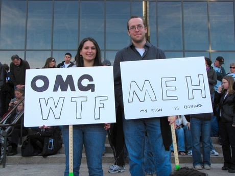 A man and woman hold signs with opposing reactions in front of the Air and Space Museum.