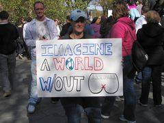 """A woman holds a sign that reads, """"Imagine a world without a--holes""""."""