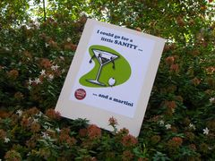 """A sign in the bushes reads, """"I could go for a little SANITY... and a martini""""."""