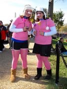 Two women dress in pink costumes designed to resemble pigs.