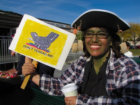 """A woman with a green-painted face wears a pirate hat adorned with used teabags, while holding a sign saying """"Don't teabag me!"""""""
